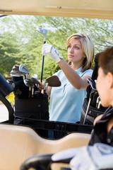 Female golfer choosing club from golf bag
