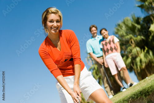 Female golfer hitting ball from sand trap