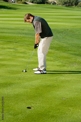 Golfer putting on golf course's green