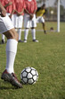Soccer player taking free kick, low section