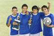 Soccer players holding trophies and ball, group portrait
