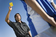 Referee holding up yellow card, portrait, low angle view