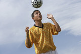 Soccer player heading ball, portrait