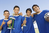 Soccer players holding trophies, group portrait