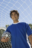 Soccer player standing in goal holding ball, portrait