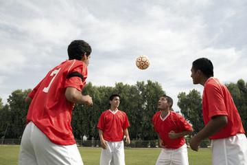 Soccer players practising heading ball