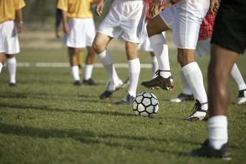 Soccer players competing for ball, low section