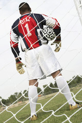 Goalkeeper standing in goal with ball, back view