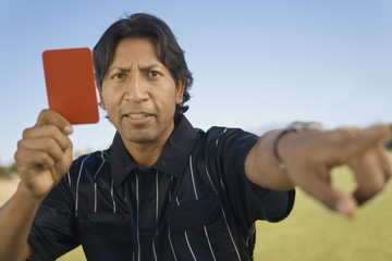 Referee holding up red card and pointing, portrait