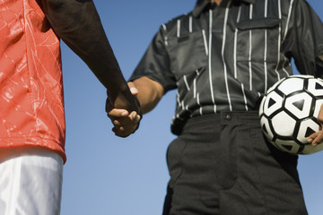 Soccer player and referee shaking hands, mid section