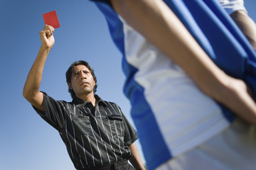 Referee holding up red card, portrait, low angle view
