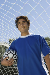 Soccer player standing in goal holding ball, portrait