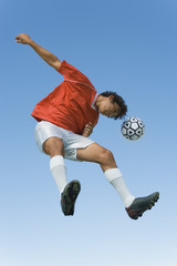 Soccer player jumping to head the ball in mid-air with blue sky background