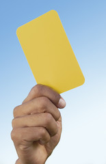 Soccer referee holding up yellow card, close-up on hand