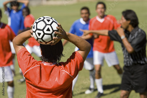 Soccer player throwing in ball, back view