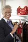 Smiling senior Woman checking out purse while Shopping