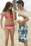 Couple Flirting on Beach with volleyball net between them, man holding ball