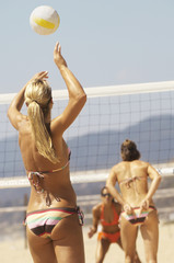 Female beach volleyball player serving volleyball, back view