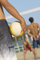 Beach volleyball player holding volleyball, preparing to serve