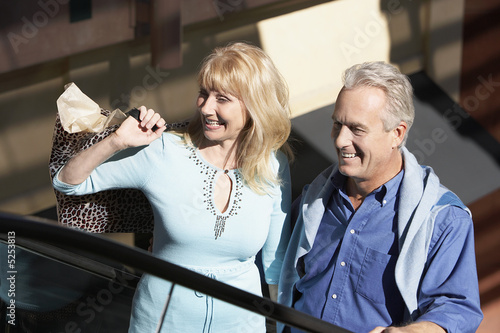 Middle-aged Couple standing side by side outside on Shopping Trip