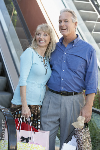 Smiling middle-aged Couple standing, arms around each other near escalator on Shopping Trip