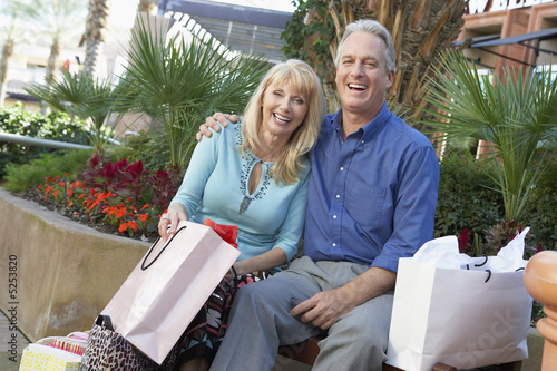 Middle-aged, Smiling couple sitting outside, arms around each other, on Shopping Trip