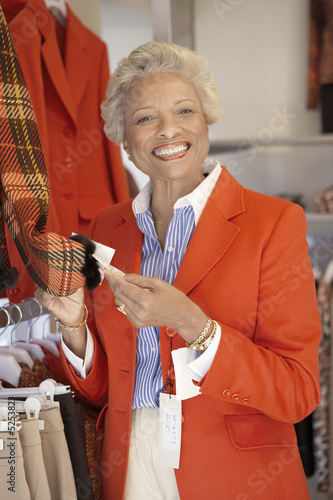 Smiling Woman checking price of blazer while Shopping