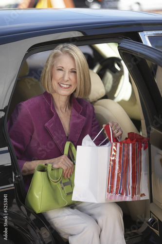 Smiling middle-aged Woman sitting in door of car, holding shopping bags