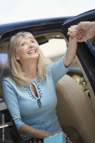 Smiling Woman getting out of car, holding Shopping Bags