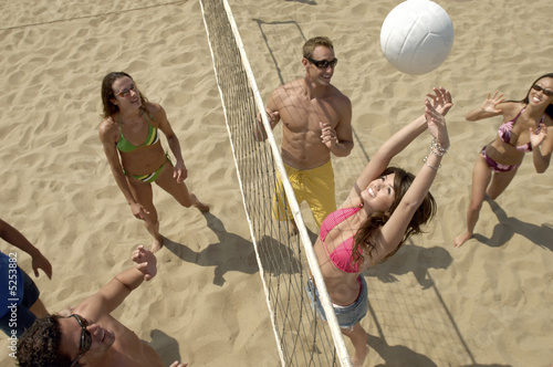 Group Playing Volleyball on Beach