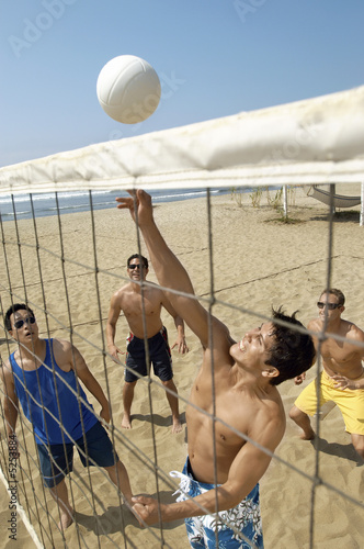 Small group of young men playing volleyball on beach