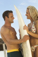 Surfer couple standing face to face, holding surfboard between them, outdoors