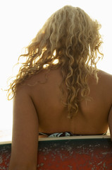 Female surfer carrying surfboard, back view, close-up