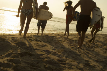 Group of Surfers Walking on Beach