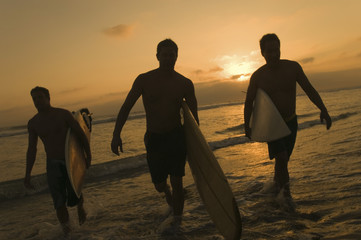 Surfers on Beach at Sunset