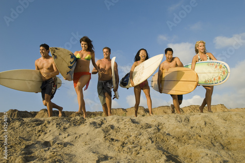 Group of Surfers Running Towards Waves