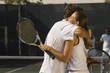 Tennis Players holding rackets, Hugging at Net, side view