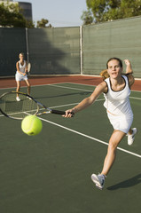 Tennis Player Reaching to hit tennis ball on tennis court