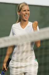 Smiling Tennis Player Pumping Her Fist, standing near net