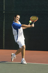 Tennis Player on court, preparing to return tennis ball with backhand