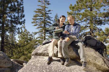 Hikers relaxing on boulder near forest