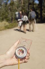 Hiker holding compass, outdoors