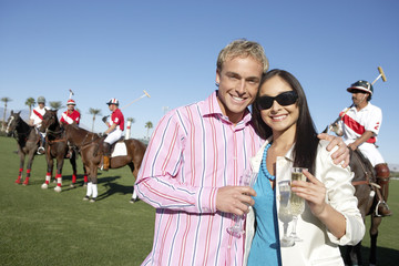 Couple standing, arms around, Celebrating with Champagne at a Polo Match