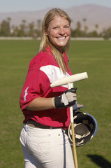 Smiling Female Polo Player standing on polo field holding polo stick and helmet, side view