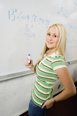 female student writing equations on whiteboard, (portrait)
