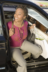 Woman with shopping bags getting out of car, portrait
