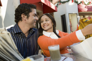Couple sitting in cafe, woman showing clothing purchase to partner