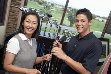 Smiling Clerk assisting mid-adult woman shopping for golf clubs in Golf Shop