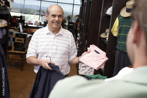 Senior Man standing in Golf Shop, asking clerk about shirt