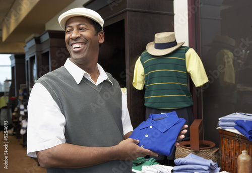 Smiling Man wearing golf apparel in Golf Shop holding shirt near manikin